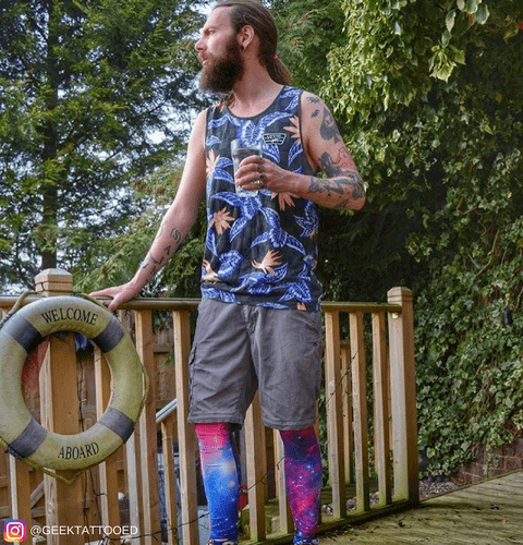 man drinking beer at festival wearing pink and blue galaxy leggings