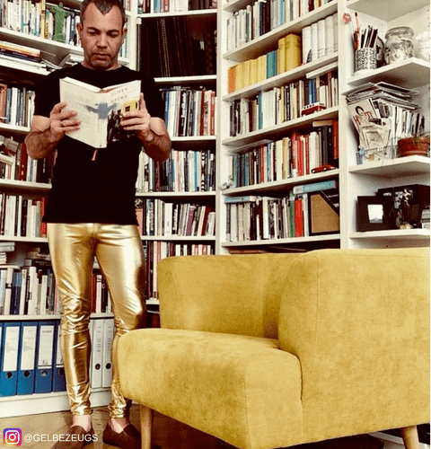 man reading book in library wearing gold metallic shiny meggings