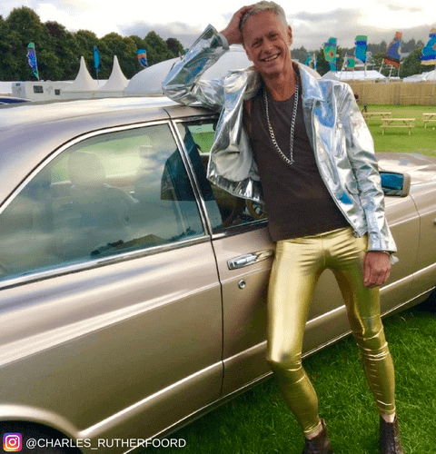 old cool guy leaning on classic car wearing gold metallic leggings for men