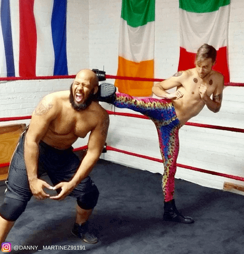 wrestler kicking opponent in colorful leopard print mens leggings