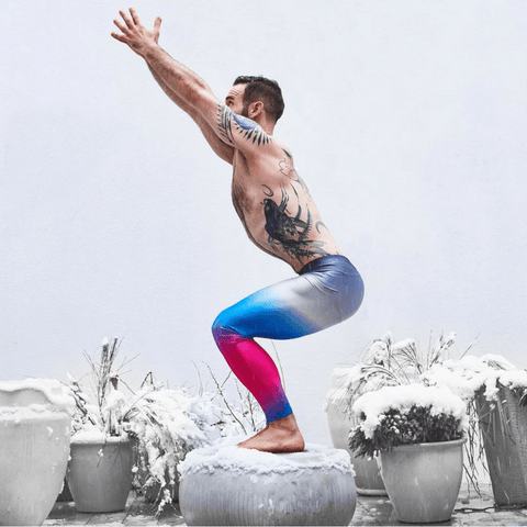 yoga dude doing sun salutation in pink blue silver coloured mens leggings