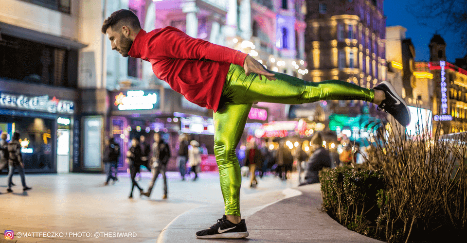 yoga pose man  wearing metallic green mens tights on street