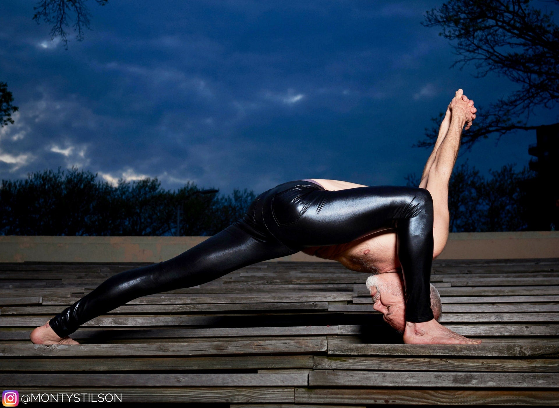 yoga man in shiny black male tights doing evening pose