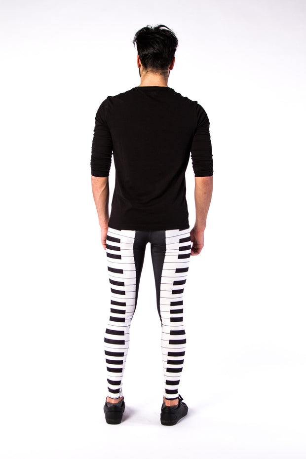 Man posing in Kapow Meggings Black and White piano key men's leggings from behind