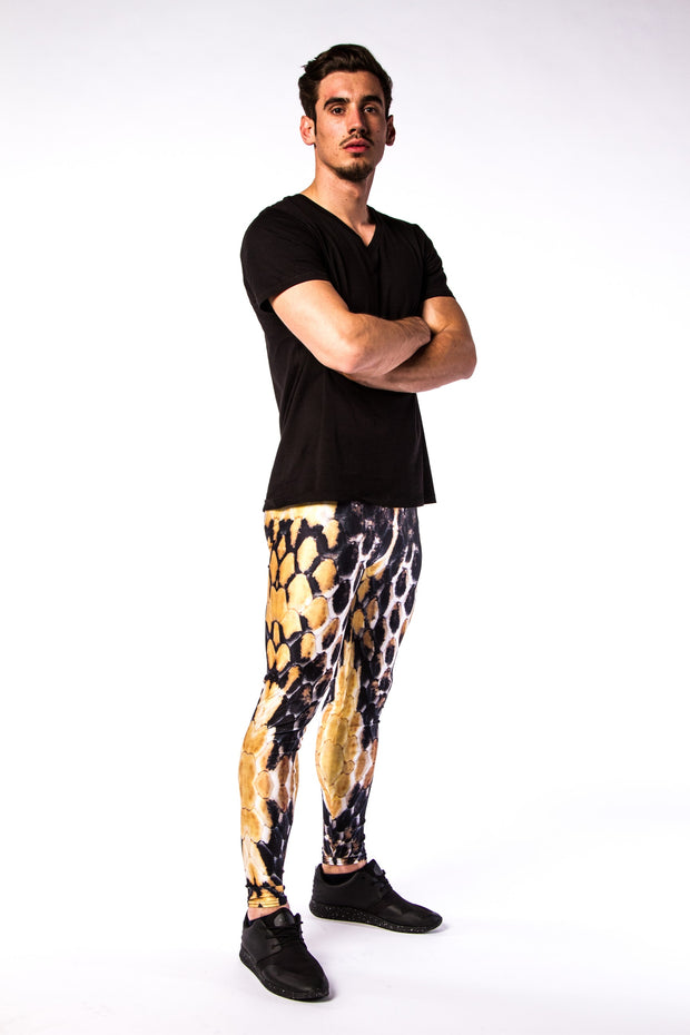 Man posing in Kapow Meggings black, white and orange beehive themed men's leggings one side view