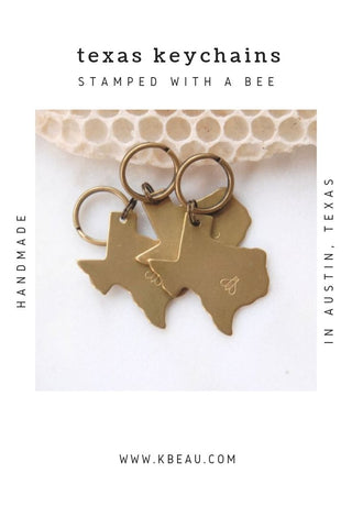 Three Texas shaped keychains with honeybee stamped on them lying on white background with honeycomb kbeau jewelry