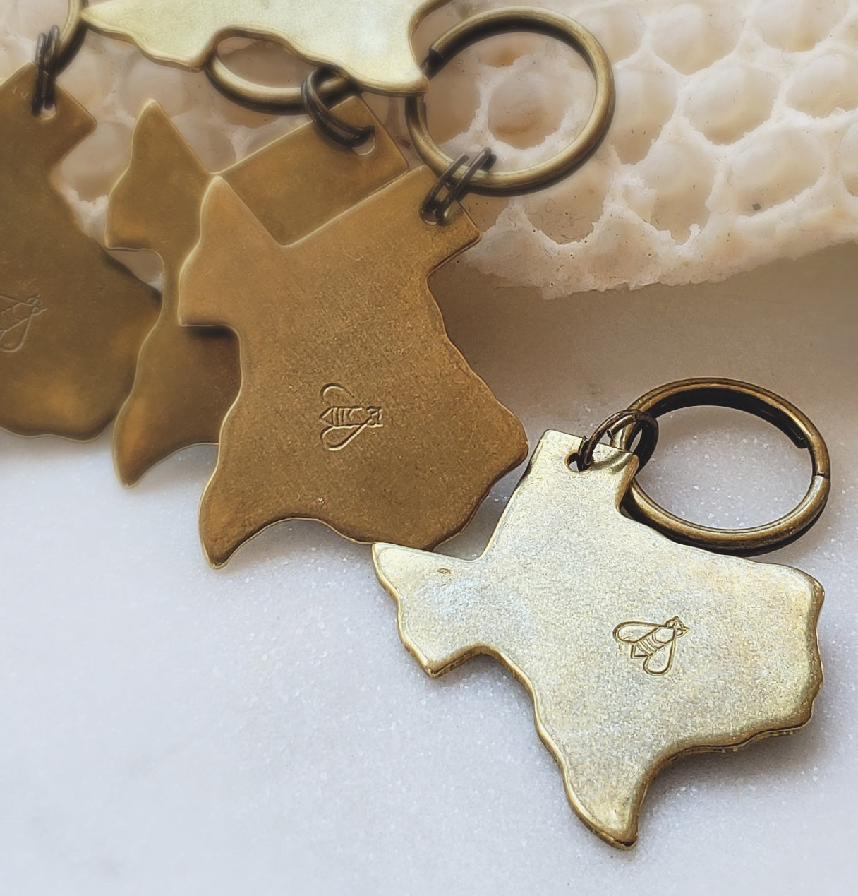 small Texas-shaped brass keychains with honeybee stamped on it white background with honeycomb