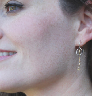 woman smiling and wearing earrings of tiny hexagons with a gold chain hanging down with a bead of citrine at the end like a honey drop