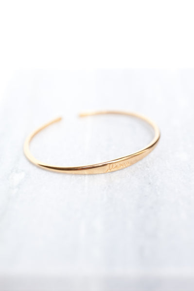 Gold cuff bracelet to remind a mother which side she last fed her baby on. The word Mama is engraved on the top of the bracelet.