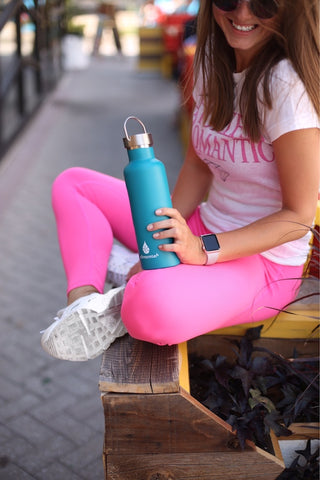 girl sitting with bottle of water to stay hydrated