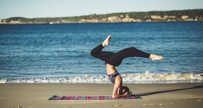 Woman doing yoga pose in athleisure wear on the sand