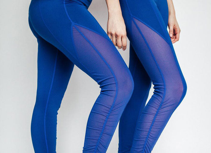 Bottom half of two women stretching in blue athleisure leggings