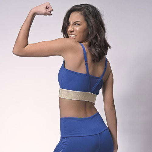 Woman flexing her arm wearing athleisure bra and bottoms