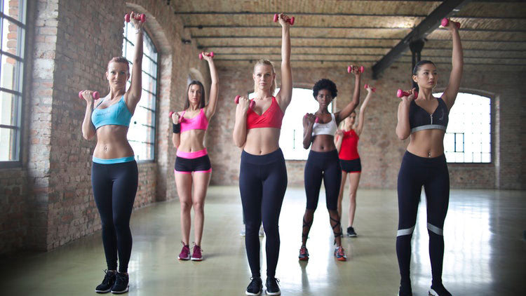 Empty room with women lifting small barbells in athleisure wear