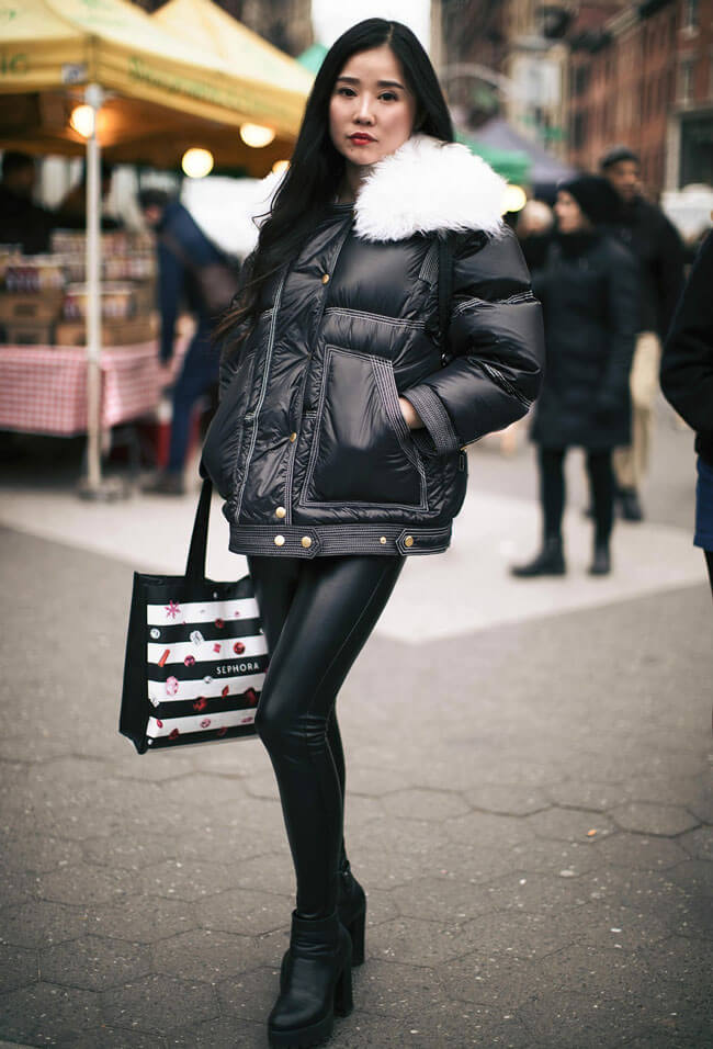 A woman in black leggings, black booties, and a black and white winter jacket