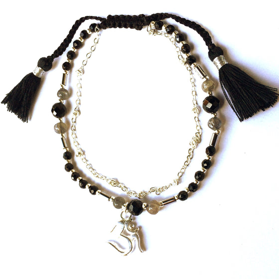 This gorgeous Seed Of Life charm bracelet is made with loving intention from healing gemstones of Smokey Quartz, Onyx & Obsidian. Featuring a hand crafted sterling silver plated OM charm