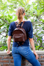 Model wearing brown croco embossed small leather backpack