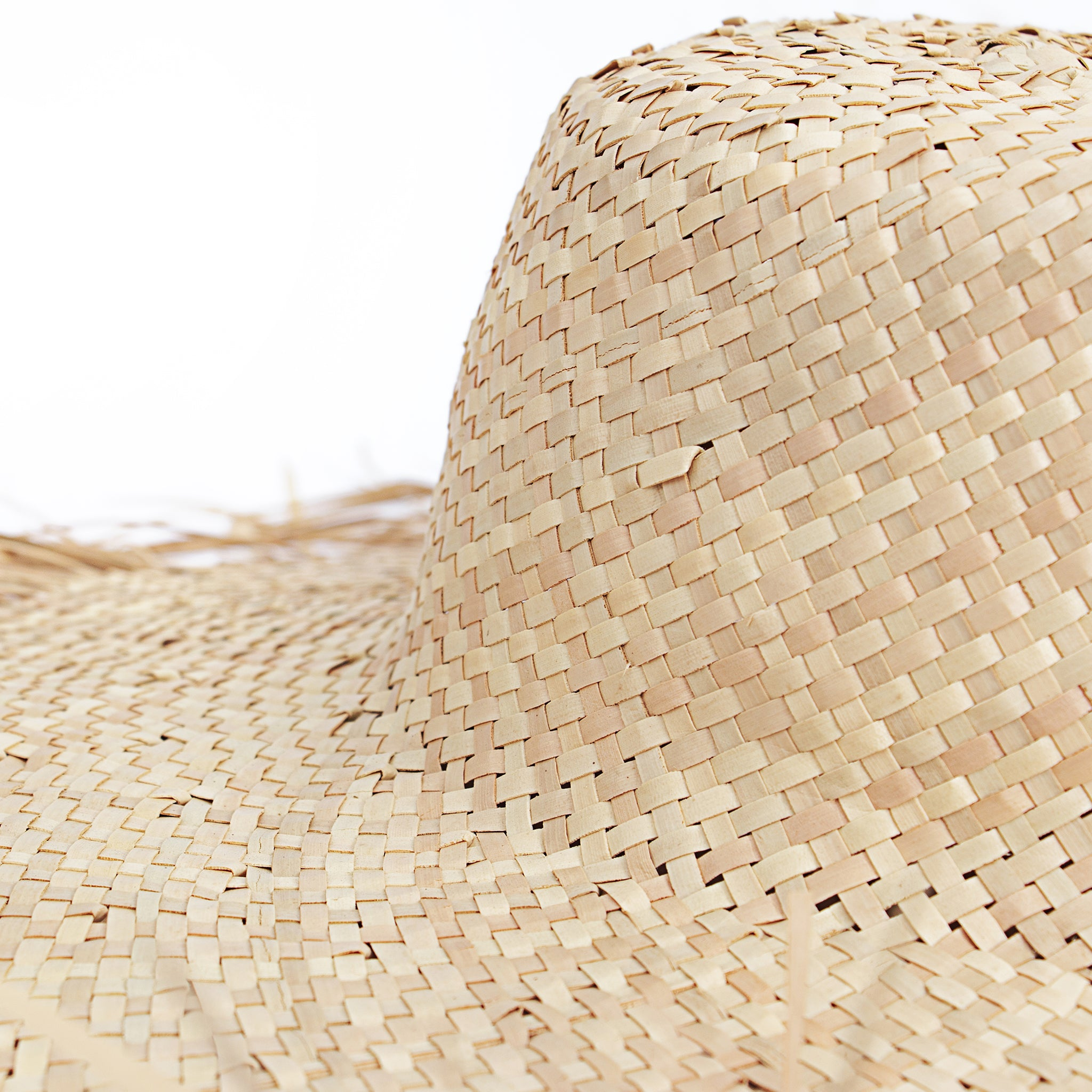 Close up view natural wide brim with frayed edge women straw raffia sun hat