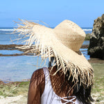 Model wearing natural color wide brim frayed edge beach straw raffia sun women hat