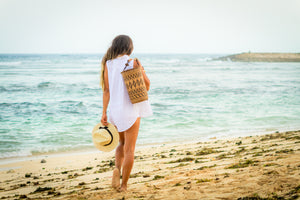 Model on beach wearing Made in Bali Woven Basket Women Backpack