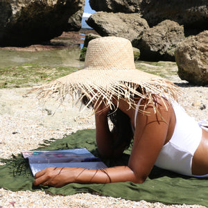 Model on the beach wearing natural color wide brim frayed edge raffia beach hat