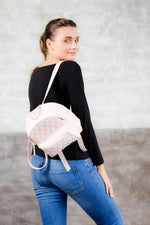 Model wearing light pink quilted leather small backpack