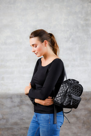 model wearing in side view black quilted leather backpack