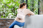 Model wearing light pink quilted leather small backpack sitting on couch