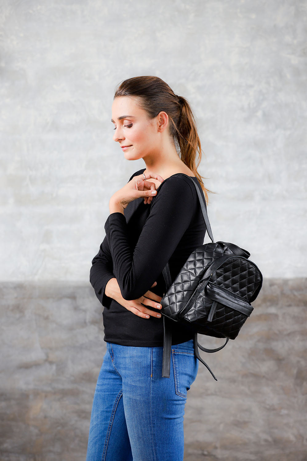 Model wearing on one shoulder black quilted leather small backpack