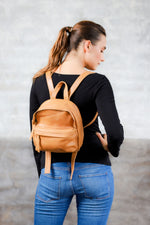 Model wearing tan genuine leather mini backpack