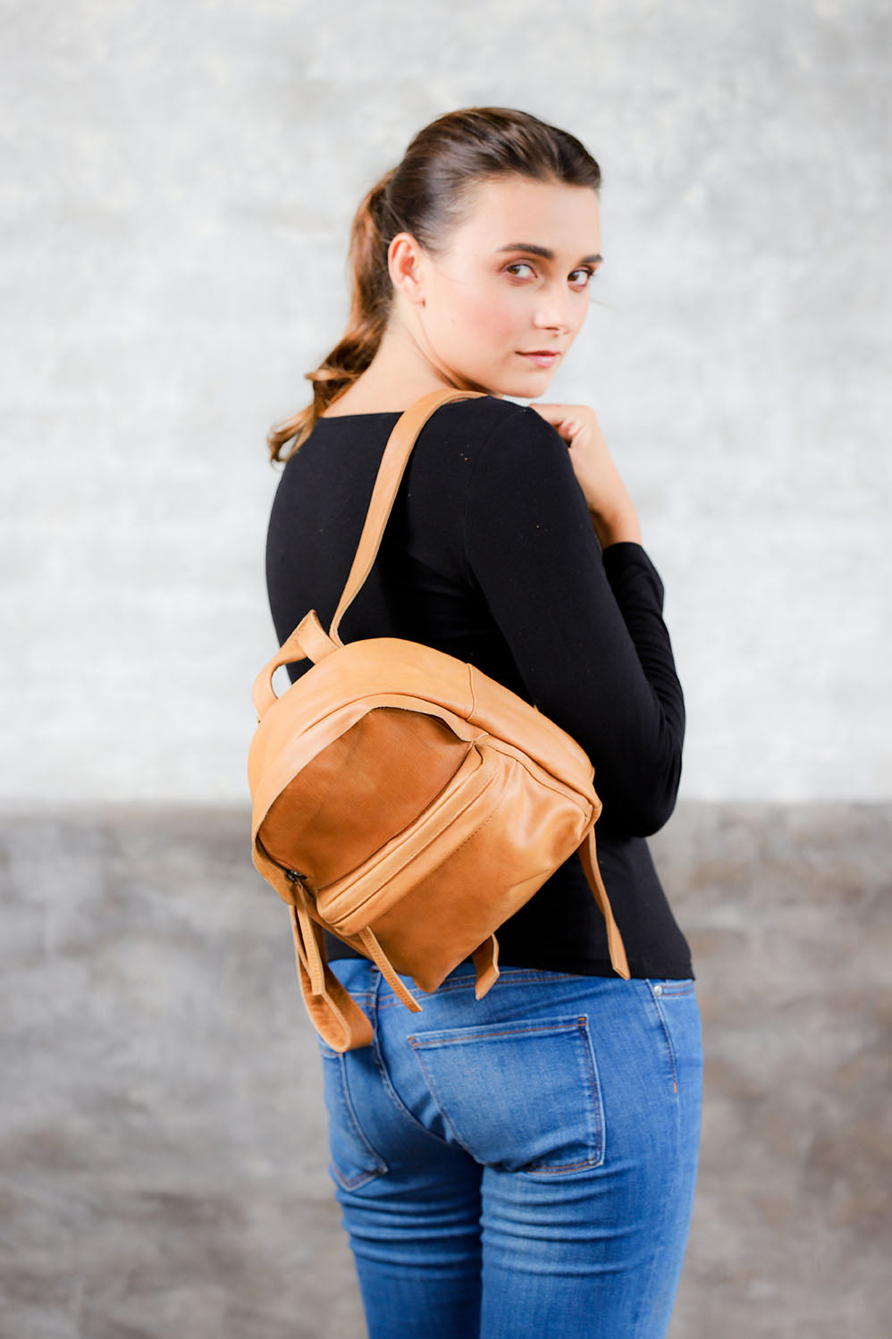 model wearing tan genuine leather mini backpack on one shoulder