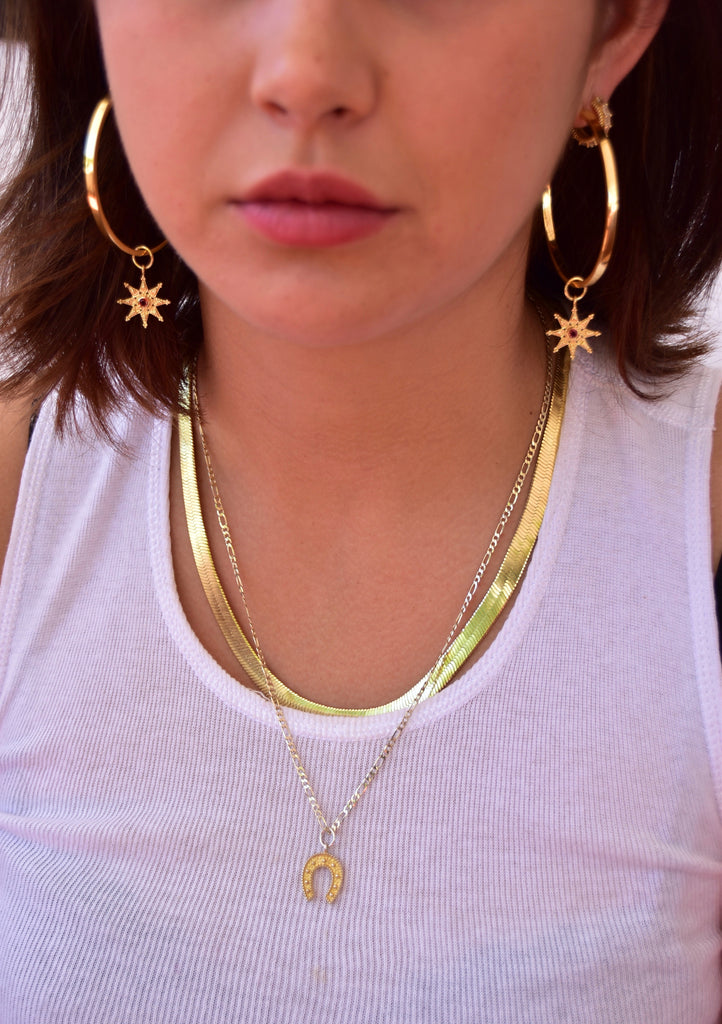 Model wearing large, thin, flat hoop statement earrings with 24K micron gold plating and interchangeable gold star charms with natural garnet stones