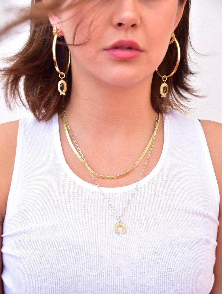 Model wearing large, thin, flat hoop statement earrings with 24K micron gold plating and interchangeable gold snake charms with smoky quartz gemstones