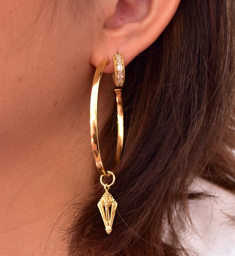 Model wearing large, thin, flat hoop statement earrings with 24K micron gold plating and interchangeable gold lantern charms