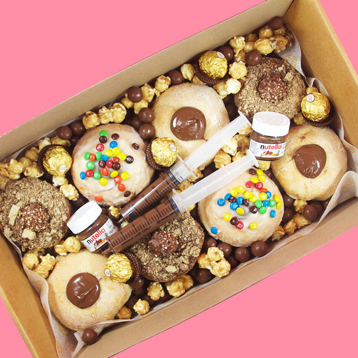 Goldeluck's Nutella x Ferrero Rocher doughnut box. This doughnut box includes 3 nutella filled doughnuts, 2 glazed Nutella doughnuts with mini M&Ms and Ferrero Rocher cronuts. This doughnut box also includes a mini Nutella jar, Nutella syringes, popcorn and Malteser choc malt balls