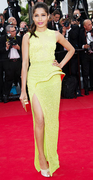Freida Pinto in a neon colored Atelier Versace gown with a thigh high slit