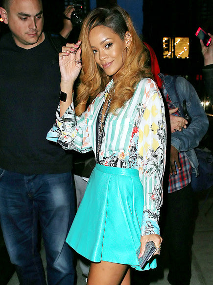 Rihanna in a bold hued leather A-line mini and printed blouse