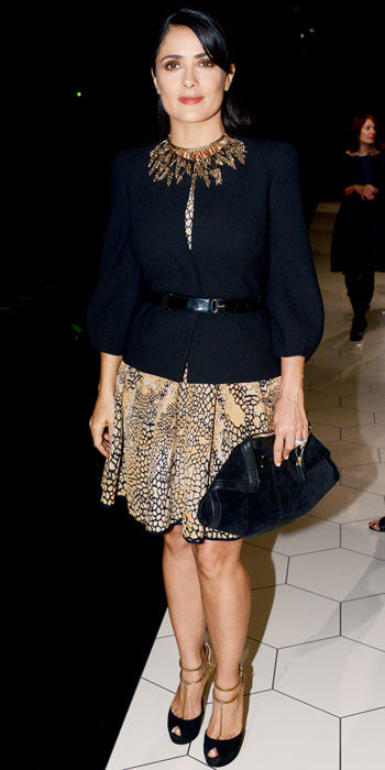 Salma Hayek Pinault attended the Alexander McQueen show in a printed dress topped with a black jacket and statement necklace