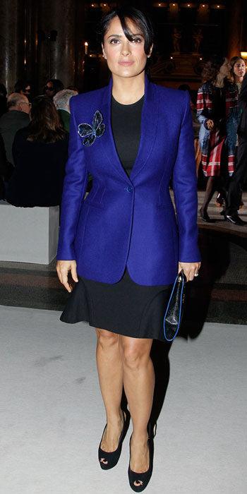 Salma Hayek attended the Stella McCartney show in a cobalt blue blazer accented with a butterfly brooch and a simple LBD