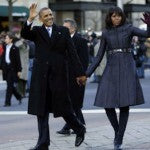 The Obamas greet the crowds at a parade following the inauguration ceremony