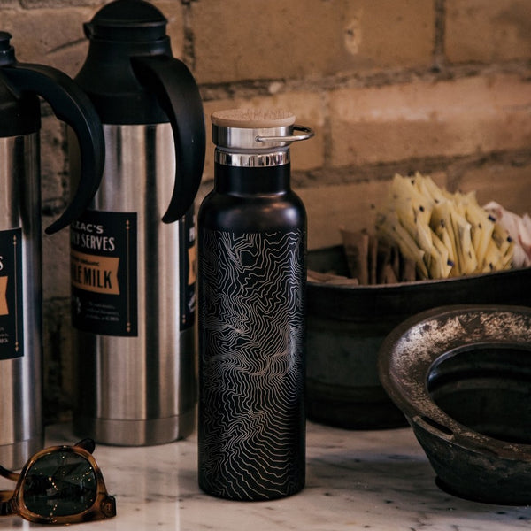 20oz Stainless Steel Insulated Bottle with Bamboo Top in Black with Custom Engraving of Map on Table with Coffee