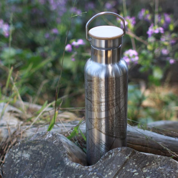 20oz Stainless Steel Insulated Bottle with Bamboo Top with Custom Engraving of Map on Tree Stump Next to Flowers