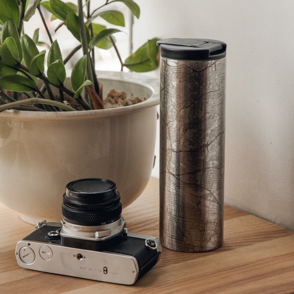17oz Stainless Steel Insulated Tumbler with Custom Engraving of Map on Table Next to Camera and Plant