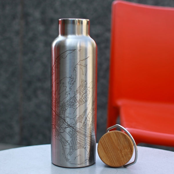 20oz Stainless Steel Insulated Bottle with Bamboo Top with Custom Engraving of Map on White Table and Red Chair