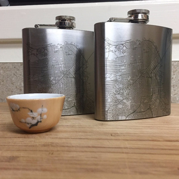 Pair of 6oz Stainless Steel Flask with Custom Engraved Map on Table Next To Sake Cup