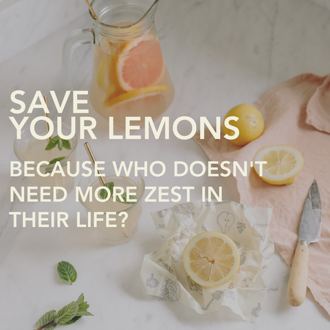 A white counter with a glass jug of citrus water and half cut lemons and grapefruits sitting on small Abeego beeswax food wraps
