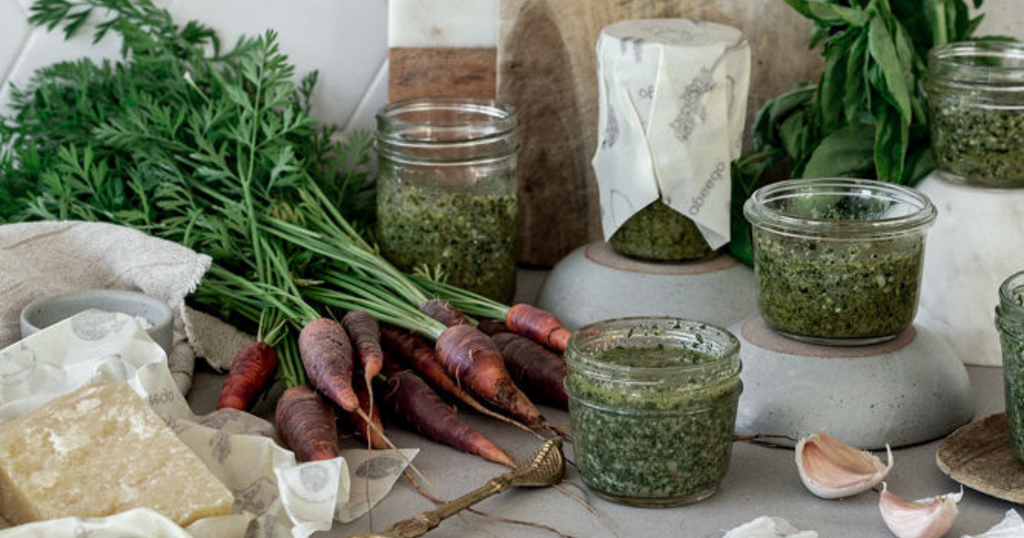 carrots, parmesan, and jars of carrot top pesto covered with Abeego food wrap