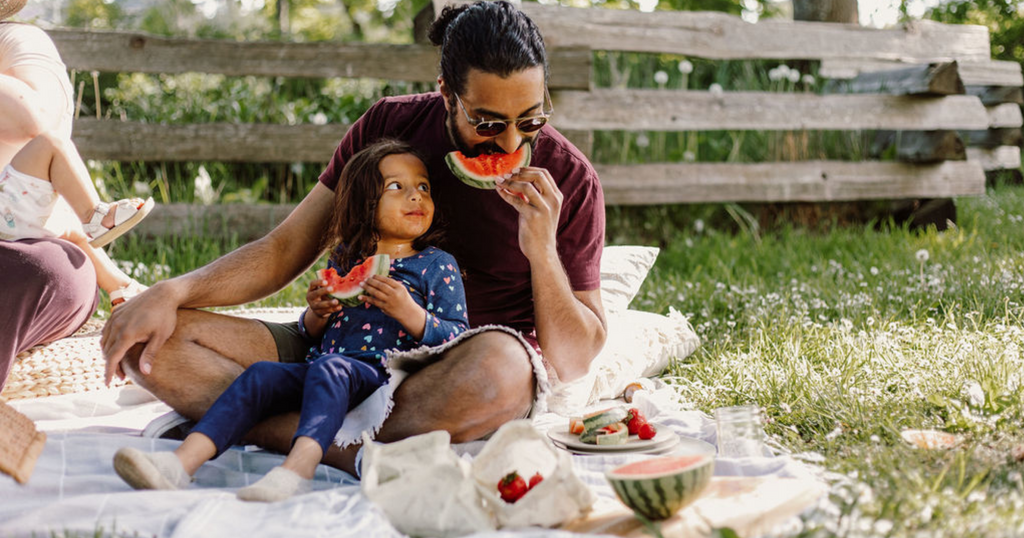 father and daughter eating watermelon together on a picnic