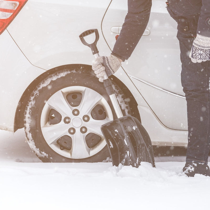 Person using snow shovel to dig out their car