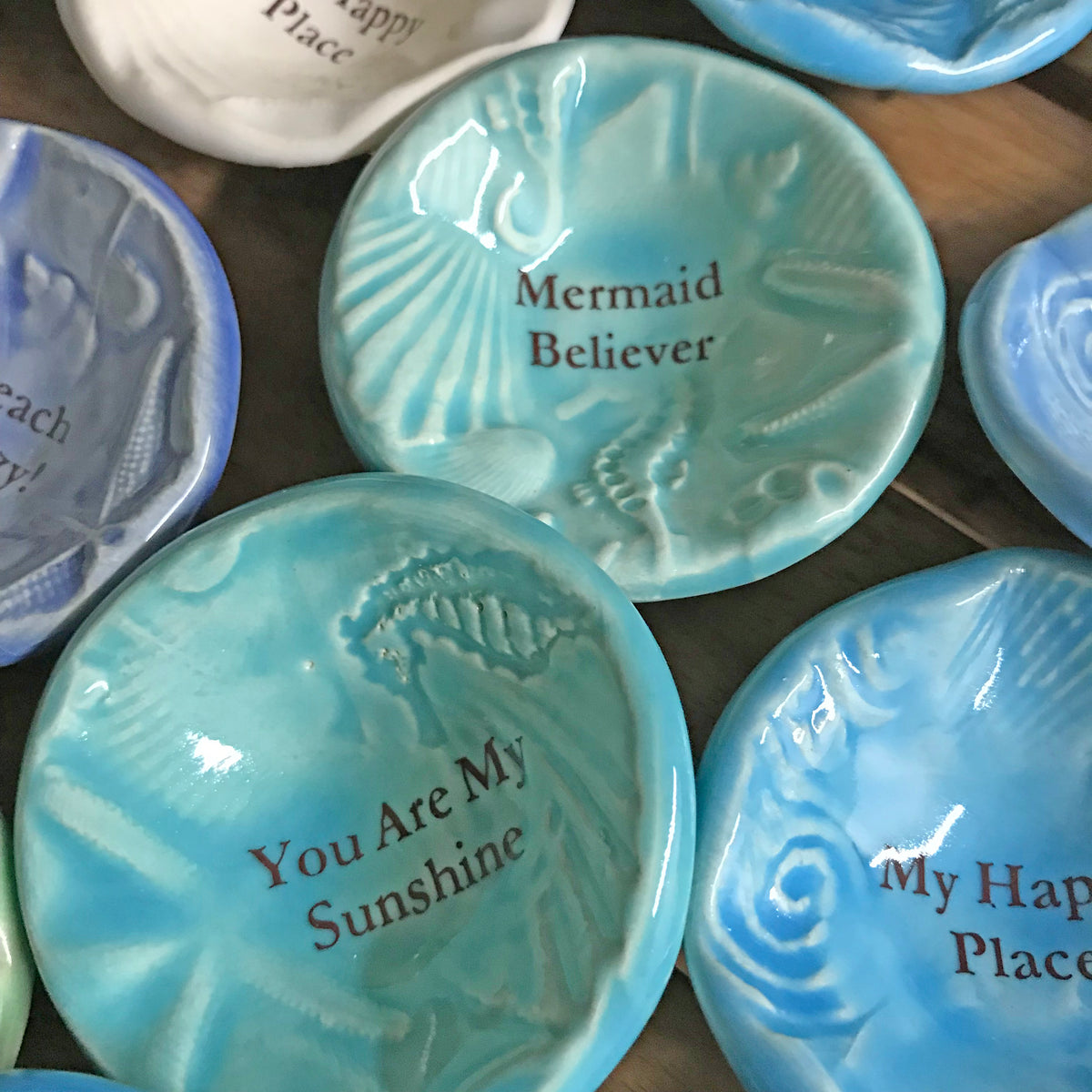 "Giving Bowls with shells, starfish and seahorse designs. come in 10 words or phrases including ""Mermaid Believer."" A"